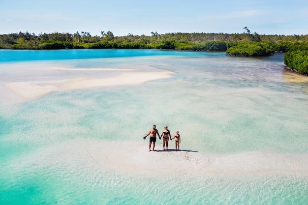 모리셔스의 열대 섬에 아이를 둔 젊은 아름다운 가족. 가족은 인도양의 작은 섬에 서 있습니다. 모리셔스 섬입니다.
