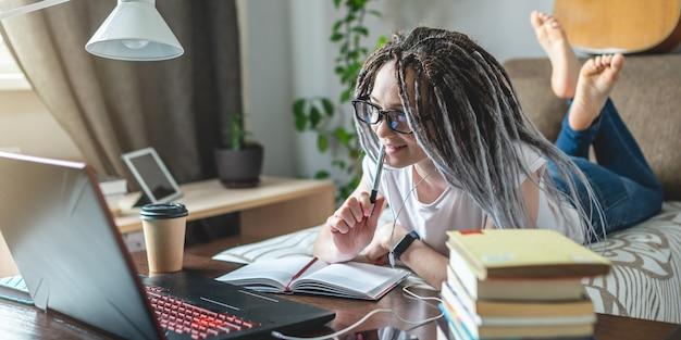 Молодая красивая студентка с дредами учится на онлайн-уроке дома в комнате с ноутбуком