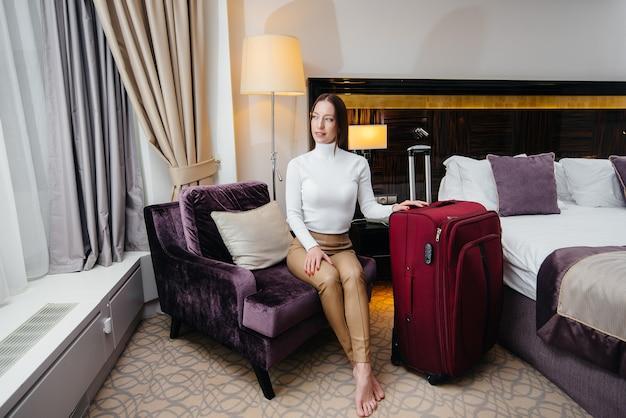 젊은 아름다운 소녀가 고급 호텔에서 그녀의 방에 체크인했습니다. 관광 및 레크리에이션.
