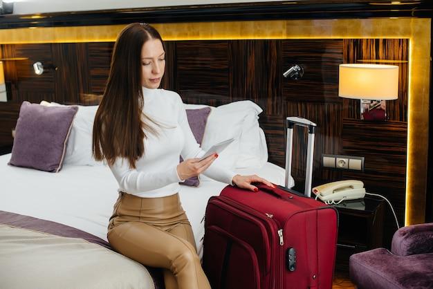 젊고 아름다운 소녀가 고급 호텔에서 그녀의 방에 체크인했습니다. 관광 및 레크리에이션.
