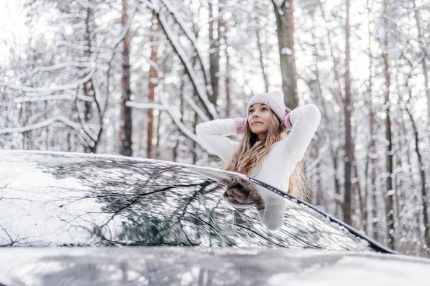 冬の雪に覆われた森の車の窓から冬の光の帽子と白いセーターを着た若い美しい少女が見えます