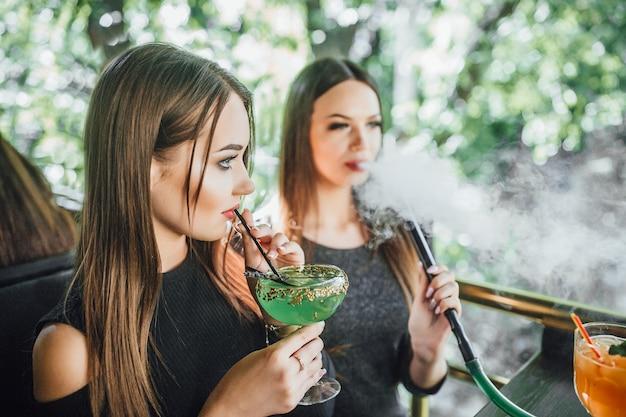 젊은 아름다운 소녀는 현대적인 카페의 여름 테라스에서 녹색 칵테일을 먹고, 그녀의 여자 친구는 물담배를 피웁니다.