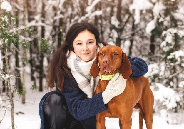 若い美しい少女は、冬の森の中で赤毛の犬を抱きしめます。動物との人間の友情