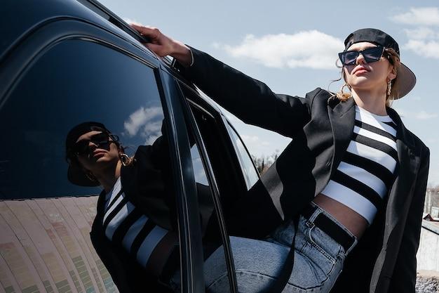 Молодая красивая девушка в черной машине смотрит в окно. стильная девушка в очках и кепке едет в машине, высунувшись из окна.