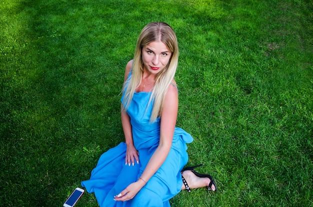 파란 드레스를 입은 아름다운 소녀가 잔디밭에 앉아 있습니다.