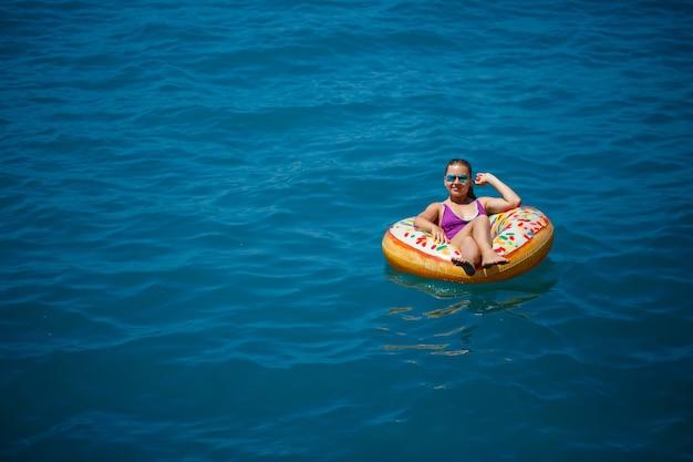 Молодая красивая девушка в ярком купальнике лежит на большом надувном кольце и плывет по синему морю в яркий солнечный летний день.