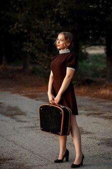 レトロなスタイルの茶色のドレスを着た若い美しい少女は、放棄された道路に彼女の手で黒いスーツケースを持って立っています。