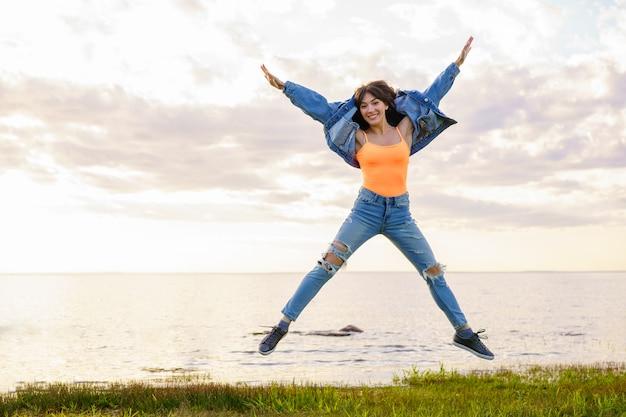 Молодая красивая девушка в джинсовой куртке, джинсах и желтой футболке прыгает на фоне моря в летний день, позирует на закате