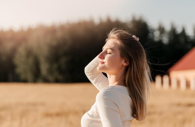 Молодая красивая девушка в джинсовой юбке идет по пшеничному полю в солнечный день