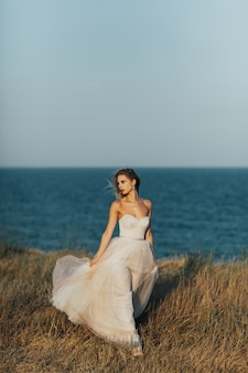 긴 창백한 장미 드레스를 입은 젊은 아름다운 소녀가 푸른 바다 표면에 대해 해변을 따라 산책합니다.