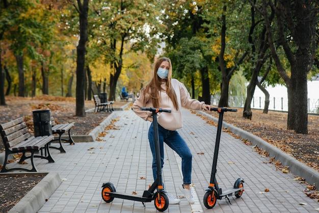 Молодая красивая девушка в маске катается в парке на электросамокате теплым осенним днем. прогулка по парку.