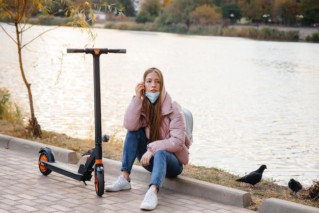 Молодая красивая девушка в маске катается в парке на электросамокате теплым осенним днем. гулять в парке.