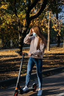 Молодая красивая девушка в маске катается в парке на электросамокате теплым осенним днем