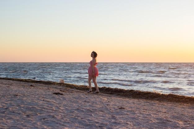 짧은 분홍색 드레스를 입은 젊은 아름다운 소녀가 일출에 빈 해변을 따라 산책합니다.