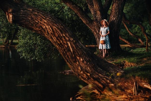 Молодая красивая девушка в соломенной шляпе и с соломенным мешком наслаждается видом на озеро.