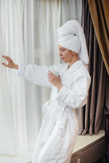 하얀 코트를 입은 아름다운 소녀가 호텔 방에서 커피를 마신다.