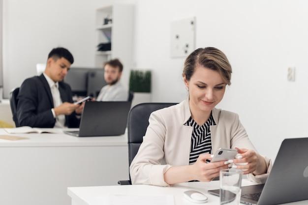 オープンスペースのオフィスにいる美しい少女は、同僚のスマートフォンからソーシャルネットワークのメッセージを受け取り、それを読みます。
