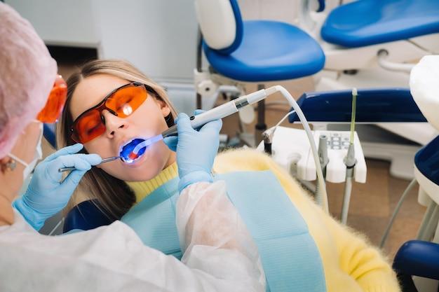 歯科用眼鏡をかけた若い美しい少女は、歯科医の歯を紫外線で治療します。フィル