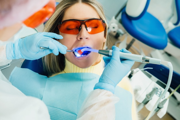 歯科用眼鏡をかけた若い美しい少女は、歯科医の歯を紫外線で治療します。歯の充填。
