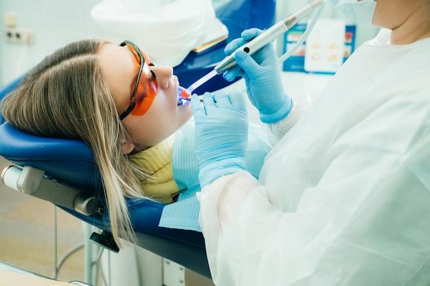 치과 안경에 젊은 아름 다운 소녀는 자외선으로 치과에서 그녀의 이빨을 취급합니다. 치아 채우기.