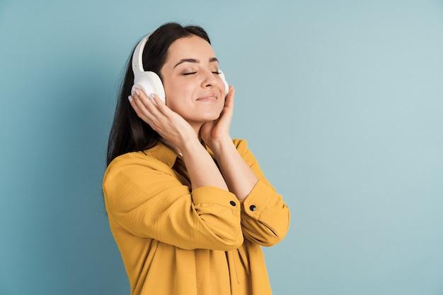 Молодая красивая девушка в наушниках слушает музыку и наслаждается ею
