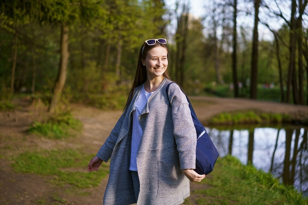 선글라스에 젊은 아름다운 소녀와 가방을 들고 화창한 날에 호수 근처의 삼림 공원에서 산책