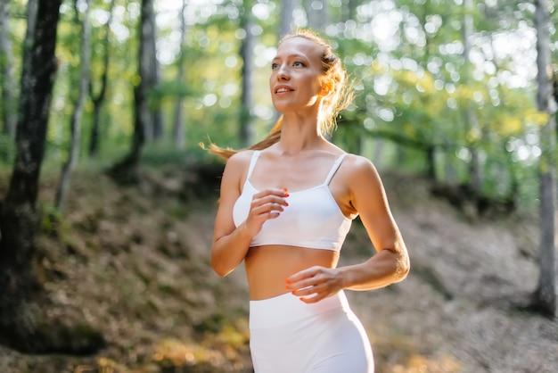 日没時に、白いスポーツ服を着た若い美しい少女が、鬱蒼とした森の道を走っています。新鮮な空気の中でスポーツをする。健康的な生活スタイル。