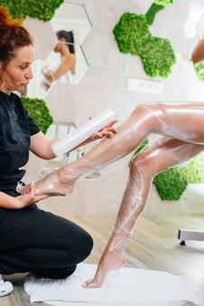 若い美しい女の子が、モダンな美容院で美容整形の全身ラップをしています。ビューティーサロンでのスパの手順。