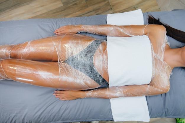 Молодая красивая девушка делает косметологическое обертывание всего тела в современном салоне красоты. спа-процедуры в салоне красоты.