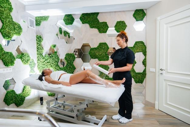 Молодая красивая девушка делает косметологическое обертывание всего тела в современном салоне красоты
