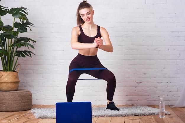 젊고 아름다운 소녀가 집에서 운동을 하고 있습니다. 소녀는 fintes 껌을 사용하여 다양한 운동을 수행합니다. 선수는 인터넷을 통해 훈련