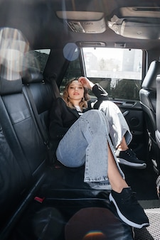 В машине сидит молодая красивая девушка. стильная девушка в костюме большого портрета, в черном салоне автомобиля.