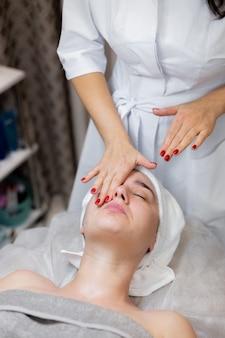 Молодая красивая девушка лежит на столе косметолога и получает процедуры - легкий массаж лица с использованием масла.