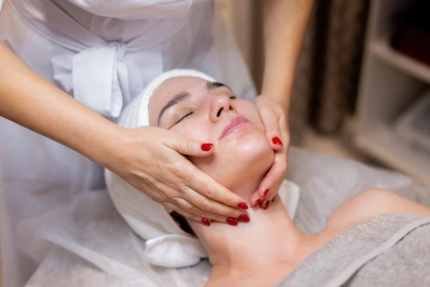 Молодая красивая девушка лежит на столе косметолога и получает процедуры, легкий массаж лица.