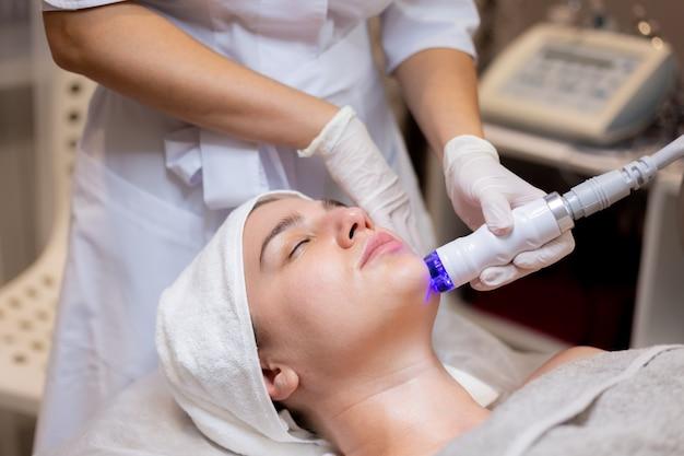 Молодая красивая девушка лежит на столе косметолога и получает процедуры
