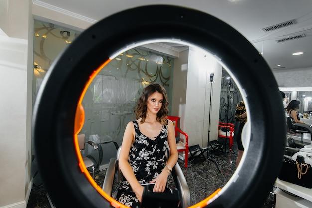 젊은 아름다운 소녀는 거울 앞에서 아름다운 저녁 화장을 합니다. 패션과 뷰티.