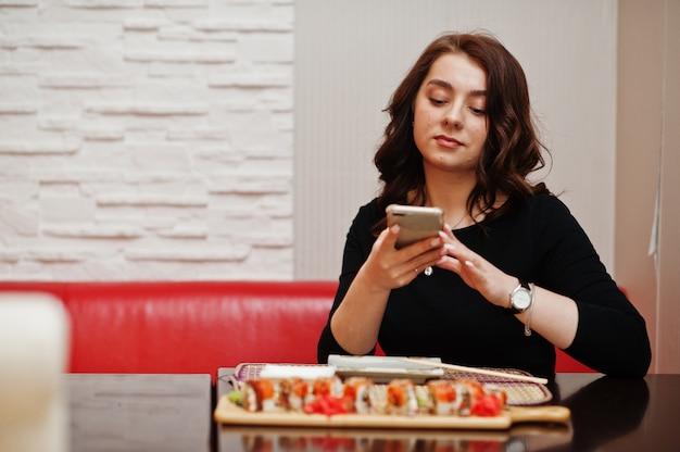 伝統的な日本食レストランで寿司の電話で写真を作る少女。