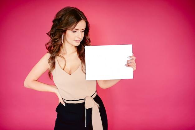 Молодая красивая девушка европейской внешности держит в руке белый пустой знак для рекламы на розовом фоне