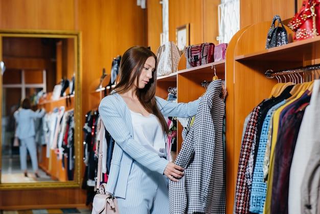 Молодая красивая девушка берет в руки одежду и ходит по магазинам.