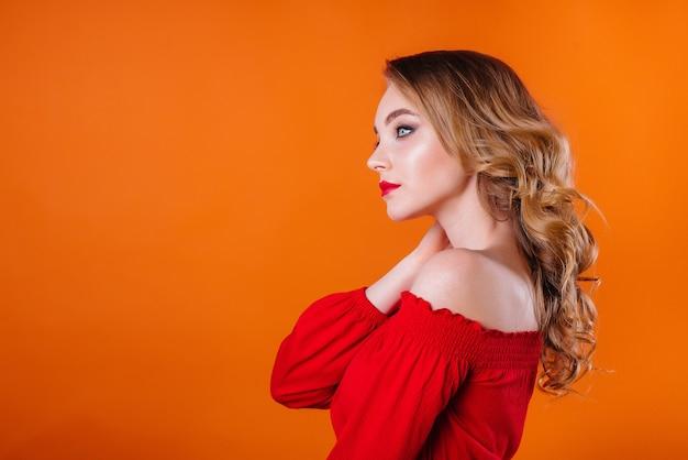 한 젊은 아름다운 소녀가 주황색 벽에 있는 스튜디오에서 감정과 미소를 보여줍니다