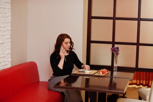 伝統的な日本食レストランで寿司を食べながら、若い美しい少女が電話で話します。