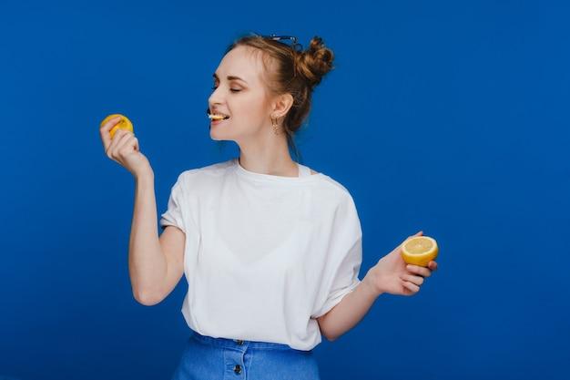 그녀의 손에 레몬을 들고 물고 파란색 배경에 서있는 젊은 아름 다운 소녀.