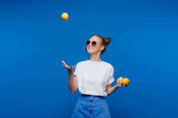 Молодая красивая девушка, стоя на синем, держа в руке лимоны. улыбается.