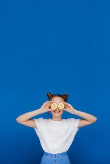 Молодая красивая девушка, стоящая на синем, держит в руках лимоны и закрывает ими глаза.