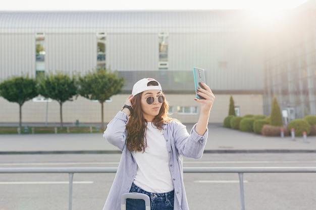 若い美しい女の子の学生が新しい都市の空港を出て、タクシーを待つ
