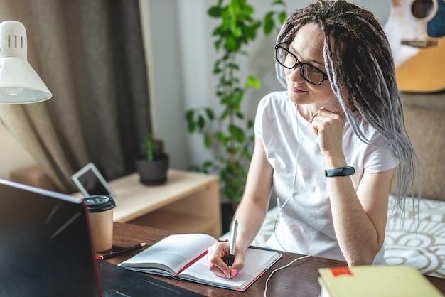 ドレッドヘアを持つ若い美しい女の子の学生は、ラップトップで自宅でオンラインレッスンで勉強しています