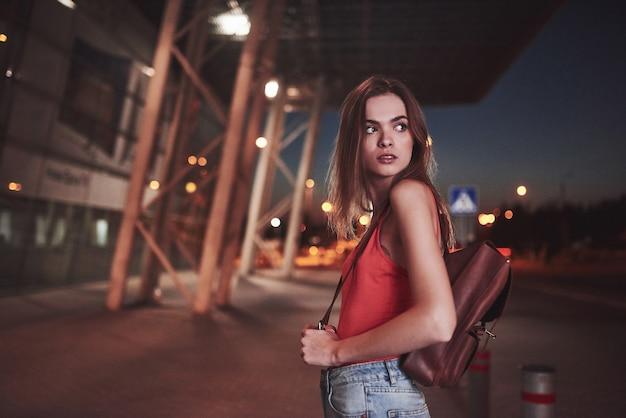그녀의 어깨 뒤에 배낭을 가진 젊은 아름다운 소녀가 따뜻한 여름 저녁에 공항이나 기차역 근처의 거리에 선다. 그녀는 막 도착하여 택시 나 친구들을 기다립니다.