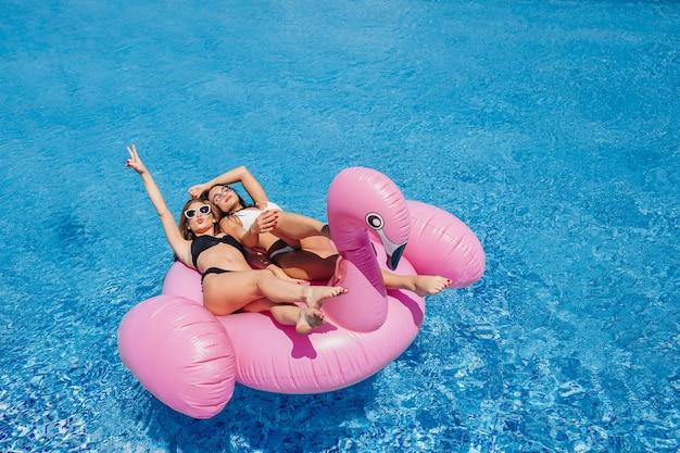 Молодая красивая девушка с красивой фигурой в черном купальнике и солнечных очках