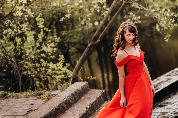 Молодая красивая девушка с длинными каштановыми волосами, в длинном красном платье спускается по лестнице у озера,
