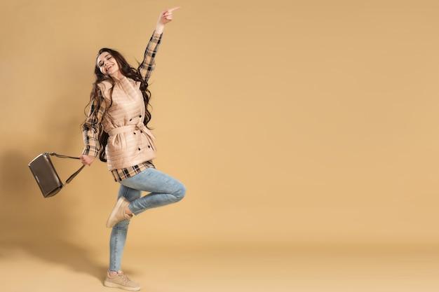 На одной ноге стоит молодая красивая девушка с длинными волосами в джинсах и бежевом жилете с сумкой в руке на пастельно-оранжевом.
